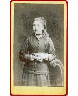 Jeune fille en queue de cheval debout, livre à la main