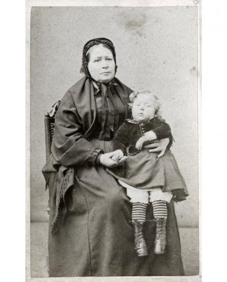 Femme en bonnet et châle avec un enfant sur les genoux