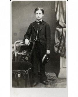 Homme debout accoudé à une chaise, chapeau à la main