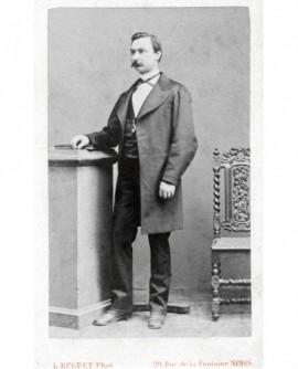 Homme moustachu debout, main sur un livre sur une selllette