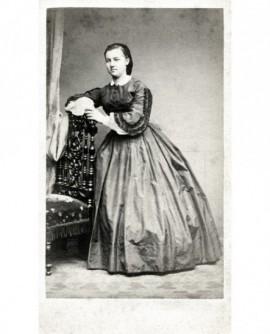 Jeune femme debout, appuyée à une chaise