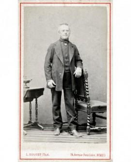 Homme à favoris, cheveux en brosse, debout accoudé à une chaise