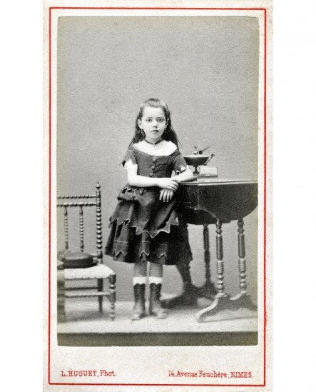 Fillette en robe à volants debout, appuyée sur une table