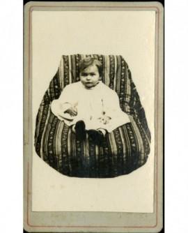 Bébé en robe et souliers, assis dans un fauteuil