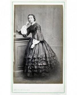 Femme en robe à volants debout, accoudée sur un meuble