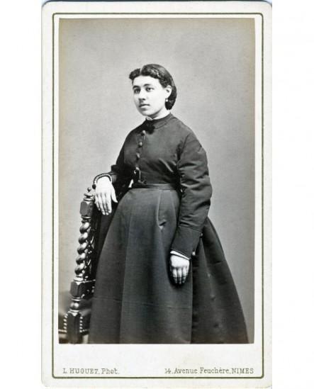 Femme (enceinte) en robe debout, appuyée sur une chaise