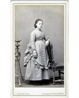 Jeune femme en robe claire debout, accoudée à une chaise