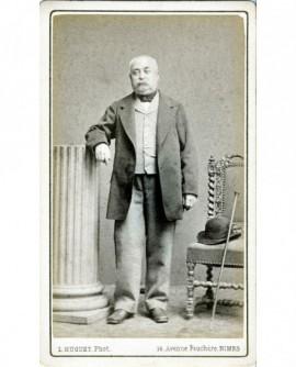Homme moustachu accoudé à une colonne (chapeau et canne)