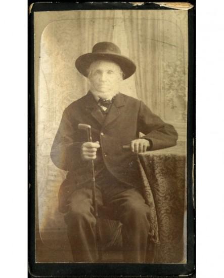 Homme âgé barbu assis, chapeau sur la tête, canne à la main