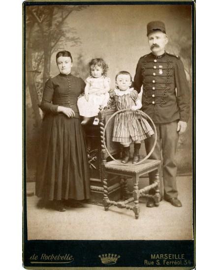 Militaire posant avec femme et enfants (jouet, cerceau)