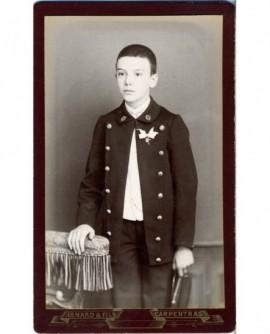 Garçon en uniforme de collégien debout, casquette à la main