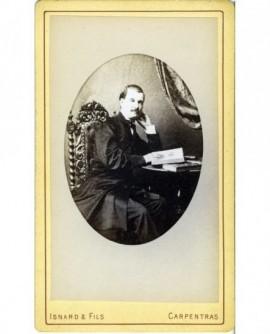 Homme moustachu assis à un bureau feuilletant un livre