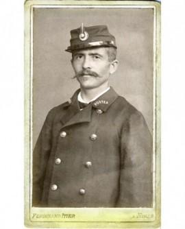 Facteur moustachu debout, en uniforme, képi sur la tête