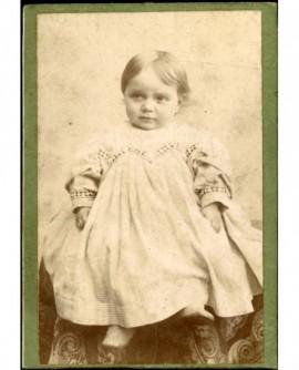 Bébé en robe et souliers assis