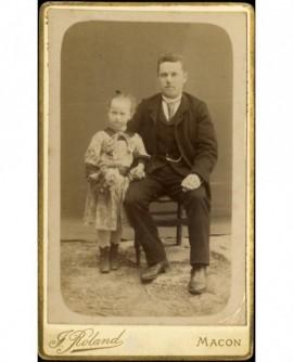Papa assis, donnant la main à sa petite fille qui tient une poupée (?)