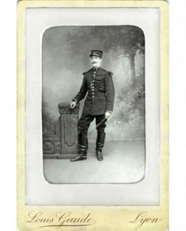 Gardien de la paix en uniforme debout, cravache et cigarette à la main (Camille Ferrand)