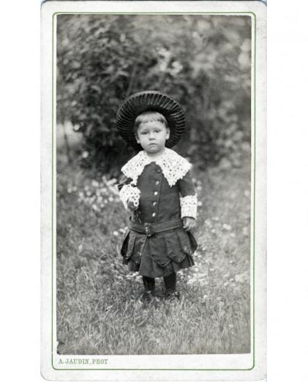 Enfant en robe et chapeau de paille debout dans un jardin