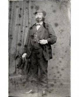 Homme à moustache et barbe chapeau sur la tête tenant sa montre