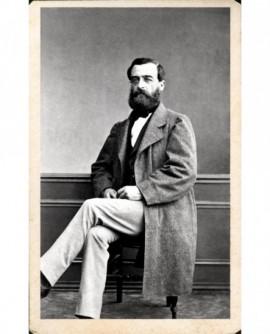 Homme barbu assis en manteau