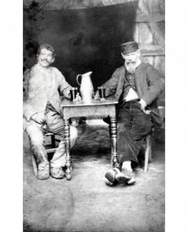 Hommes en sabots attablés devant verre et broc