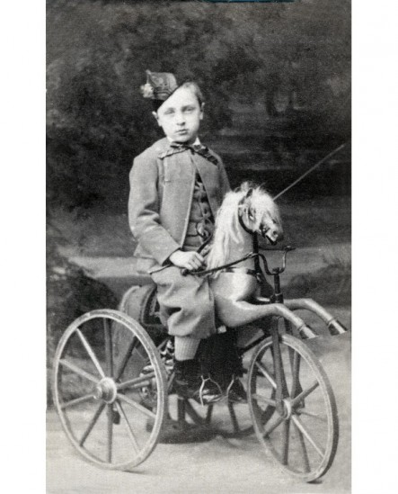 Enfant en calot sur un tricycle-cheval de bois
