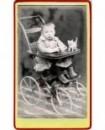 Enfant en robe et bottines assis dans une poussette, avec un petit chat (jouet) sur sa tablette