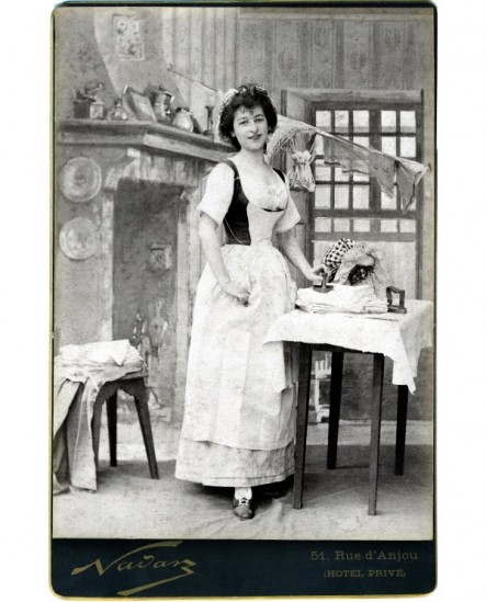Femme lingère debout tenant un fer à repasser