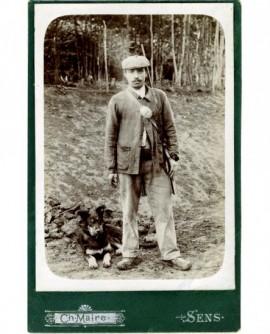 Garde-chasse moustachu debout, plaque en bandoulière, fusil sur l'épaule, chien à ses pieds