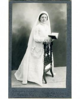 Communiante agenouillée sur un prie-Dieu, chapelet et missel en mains