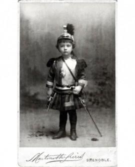 Enfant en cuirassier casqué, avec sabre et pistolet