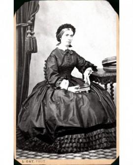 Femme en robe à volants et bonnet assise livre à la main