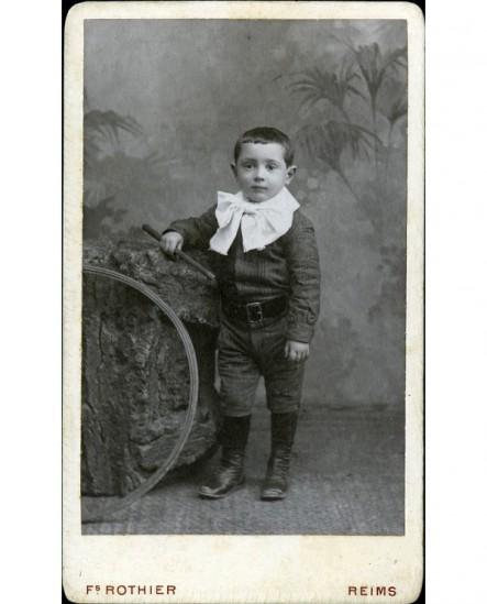 Garçon au col blanc posant avec baguette et cerceau