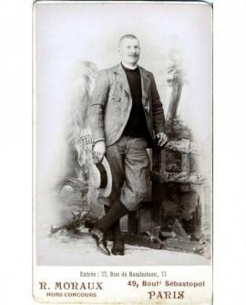Homme moustachu debout, canotier à la main