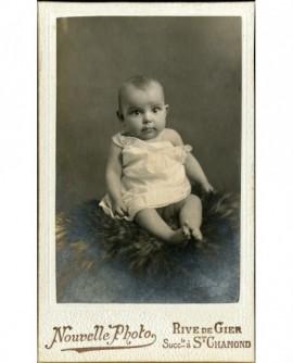 Bébé en chemise, épaule dénudée, assis sur une fourrure