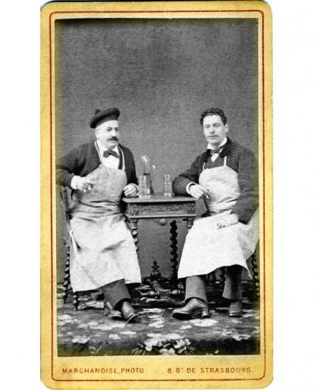 Deux hommes en tablier attablés devant deux verres