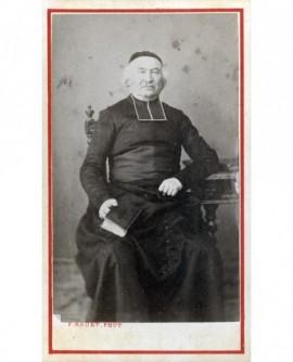 Ecclésiastique en calotte assis bréviaire à la main