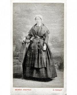Femme en robe debout accoudée à un fauteuil