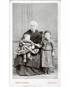 Femme en coiffe assise (nourrice?) avec deux enfants
