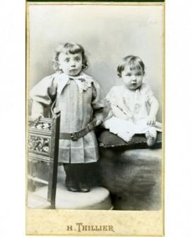 Deux enfants (un en robe à ceinturon debout, l'autre bébé assis)