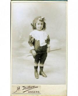 Fillette en costume de garçon debout, tenant une canne