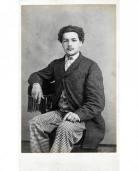 Jeune homme chassieux à la moustache naissante, assis