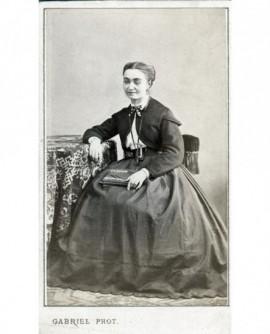 Femme en jupe et veste assise accoudée, livre sur les genoux