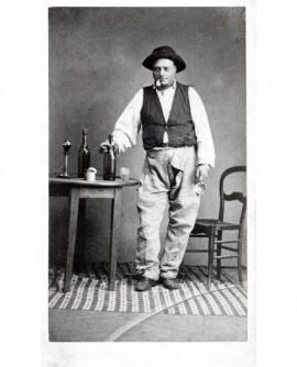 Homme débraillé chapeau sur la tête et pipe au bec, tastevin à la main