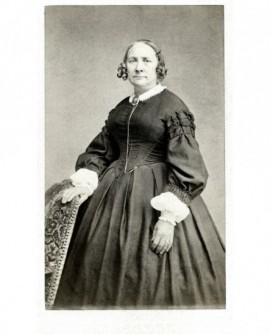 Femme en robe coiffée en macarons, appuyée sur un fauteuil