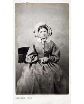 Femme en robe et bonnet noué assise, mains croisées