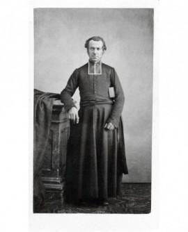Ecclésiastique en rabat debout, bréviaire sous le bras