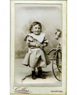 Enfant en robe près d\'un tricycle-cheval en bois (jouet)