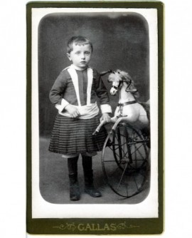 Enfant en robe à bretelle tenant un tricycle-cheval (jouet)