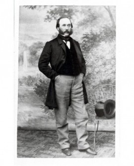 Homme à favoris debout, haut de forme sur chaise. M. Durand