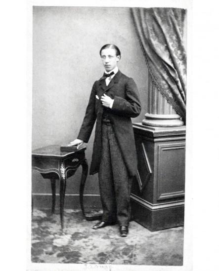Jeune homme en habit debout, la main sur un livre